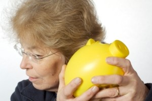 Senior Holding Yellow Piggy Bank