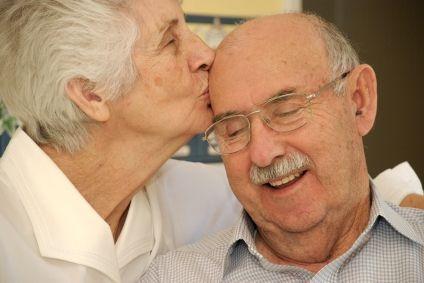 Senior Woman Kisses Senior Man on Head