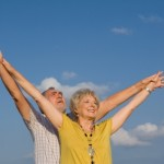 Senior Couple with Arms Raised to Sky