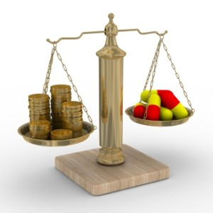 Scale Comparing Money vs Medicine Capsules